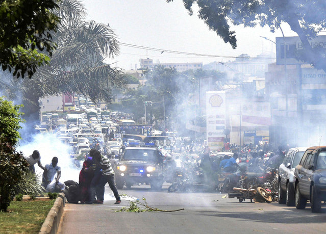 Ugandan police fires tear gas in Kampala on February 15, 2016 to disperse opposition supporters as they arrested a top presidential challenger, Kizza Besigye, days ahead of presidential polls. The Daily Monitor newspaper reported he was arrested after trying to hold a rally in the centre of the capital, which police blocked. Besigye, a three-time failed presidential candidate, has been repeatedly arrested in the past, and is commonly released without charge hours later. (Photo by Isaac Kasamani/AFP Photo)