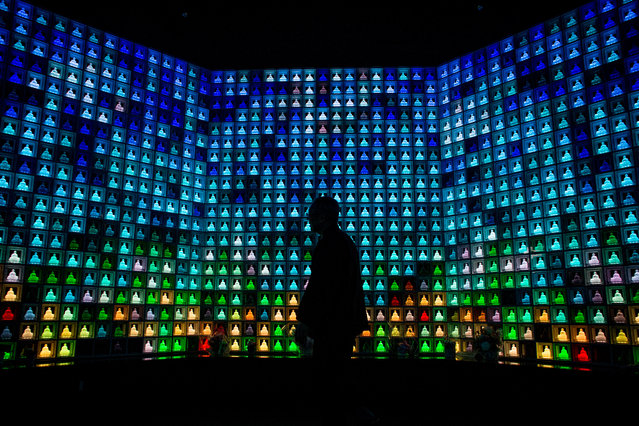 Koukokuji temple head priest Yajima Taijun walks through the Ruriden columbarium as  glass Buddha alters are lit up on April 6, 2015 in Tokyo, Japan. The Ruriden, operated by the Koukokuji buddhist temple, took two years to build and houses 2046 futuristic alters with glass buddha statues that correspond to drawers storing the ashes of the deceased. (Photo by Chris McGrath/Getty Images)