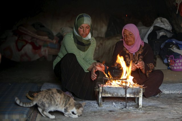 Palestinians warm themselves by a fire as they make tea inside a cave they live in, during a snow storm in West Bank village of Mufagara, south of Hebron January 27, 2016. (Photo by Mussa Qawasma/Reuters)