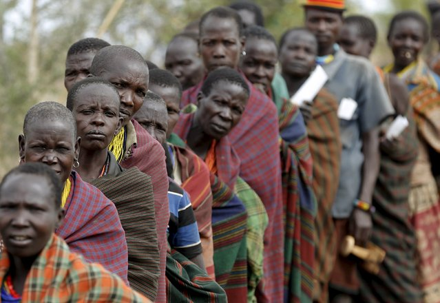 People from Karamojong tribe wait in line to vote at a polling station during elections in a village near the town of Kaabong in Karamoja region, Uganda February 18, 2016. (Photo by Goran Tomasevic/Reuters)