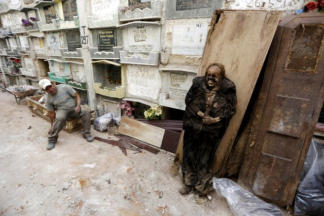 A grave cleaner sits on a coffin next to a mummified body during the exhumation work at the General Cemetery in Guatemala City, April 15, 2015. If a lease on a grave has expired or not been paid, grave cleaners will break open the crypts to remove and rebury the bodies. (Photo by Jorge Dan Lopez/Reuters)