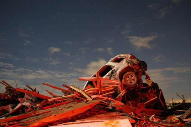 A vehicle sits on a pile of debris from the destruction caused by a tornado that touched down in Washington, Illinois. (Photo by Jim Young/Reuters)