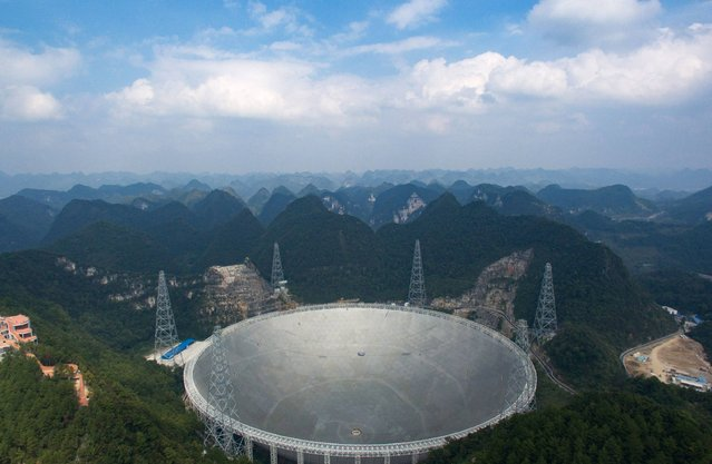 This picture taken on September 24, 2016 shows the Five-hundred-metre Aperture Spherical Radio Telescope (FAST) in Pingtang, in southwestern China's Guizhou province. Humanity's best bet at detecting aliens is a giant silver Chinese dish the size of 30 football fields – one that simultaneously showcases Beijing's abilities to deploy cutting-edge technologies and ignore objectors' rights as it seeks global prominence. (Photo by AFP Photo/Stringer)