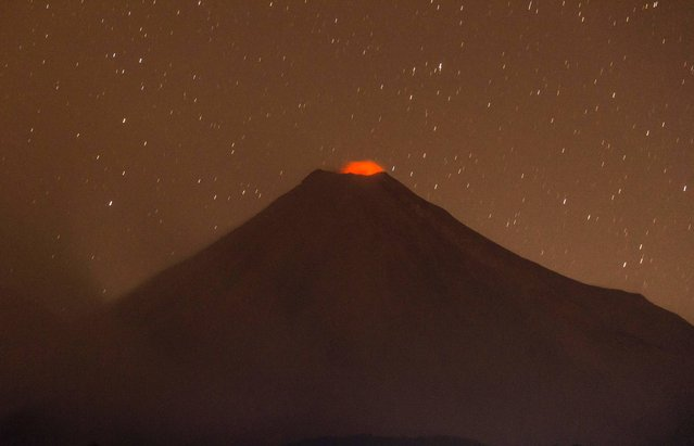 Picture of the Colima Volcano, also known as the Volcan de Fuego (Fire Volcano), taken from the community of Carrizalillo, Colima State, Mexico, early on January 23, 2017. The Colima is one of the most active volcanoes in Mexico and in the last days its activity has intensified. (Photo by Hector Guerrero/AFP Photo)