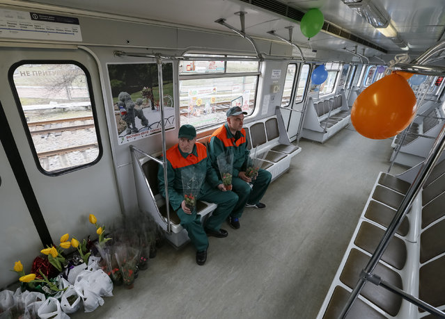 Kiev's subway staff waits for female passengers in order to offer them flowers ahead of the International Women's Day in Kiev, Ukraine, March 2, 2016. (Photo by Gleb Garanich/Reuters)