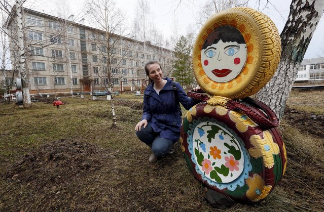 English teacher Laura Thomas, who is a British citizen, poses for a picture near a traditional Matryoshka doll made of used tyres near her campus on a day off in the town of Lesosibirsk, north of the Russian Siberian city of Krasnoyarsk, April 23, 2015. (Photo by Ilya Naymushin/Reuters)