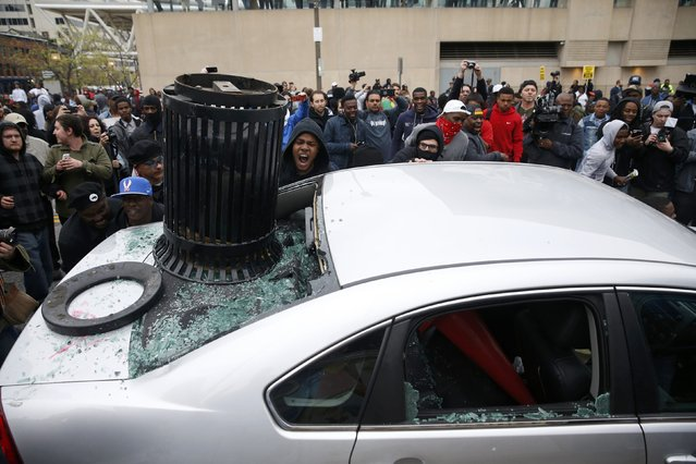 Protesters damage a car at a rally to protest the death of Freddie Gray who died following an arrest in Baltimore, Maryland April 25, 2015. (Photo by Shannon Stapleton/Reuters)