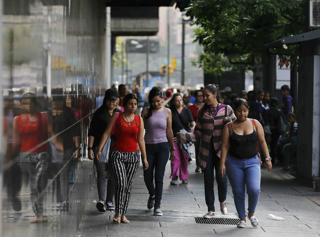 Pedestrians walk to their destination amid the country's worst-ever power outage, in Caracas, Venezuela, Friday, March 8, 2019. President Nicolas Maduro ordered schools and all government entities closed and told businesses not to open to facilitate work crews trying to restore power. (Photo by Fernando Llano/AP Photo)