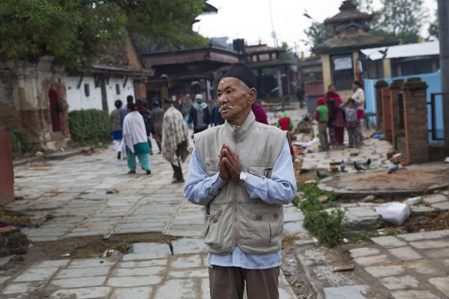 A Nepalese elderly man prays next to a building damaged in Saturday's earthquake, not pictured, in Kathmandu, Nepal, Monday, April 27, 2015. A strong magnitude earthquake shook Nepal's capital and the densely populated Kathmandu valley on Saturday devastating the region and leaving tens of thousands shell-shocked and sleeping in streets. (Photo by Bernat Armangue/AP Photo)