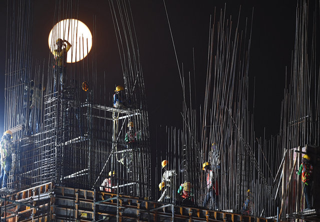 """A """"Super Snow Moon"""" rises as Indian construction labourers work at a building site in Kolkata on February 19, 2019. Super Moon is a term used when a full moon is at or near its closest approach to Earth. (Photo by Dibyangshu Sarkar/AFP Photo)"""