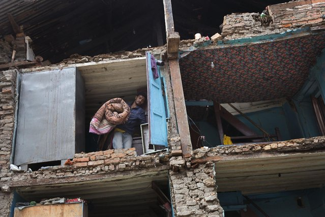 A resident carries his belongings retrieved from the ruins of his home after Saturday's earthquake in Bhaktapur, Nepal, Tuesday, April 28, 2015. (Photo by Bernat Armangue/AP Photo)