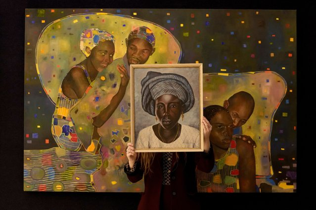 """A Bonhams employee holds a painting called """"Portrait of a Yoruba Lady"""" by Akinola Lasekan in front of a painting called """"The willing & unwilling"""" by Joseph Ntensibe at the auction rooms in London, Friday, October 8, 2021. The paintings will be up for auction in Bonhams Modern and Contemporary African Art Sale on Oct. 12. (Photo by Kirsty Wigglesworth/AP Photo)"""