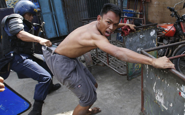 A policeman detains a squatter dweller during clashes at a squatter district in Quezon city, Metro Manila January 27, 2014. Dozens were hurt during clashes triggered by the demolition of a squatter settlement for business developments in suburban Quezon city on Monday, local media reported. (Photo by Erik De Castro/Reuters)
