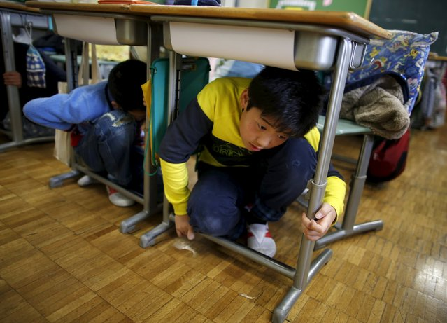 School children take shelter under desks during an earthquake simulation exercise in an annual evacuation drill at an elementary school in Tokyo March 11, 2016, to mark the five-year anniversary of the March 11, 2011 earthquake and tsunami that killed thousands and set off a nuclear crisis. (Photo by Issei Kato/Reuters)