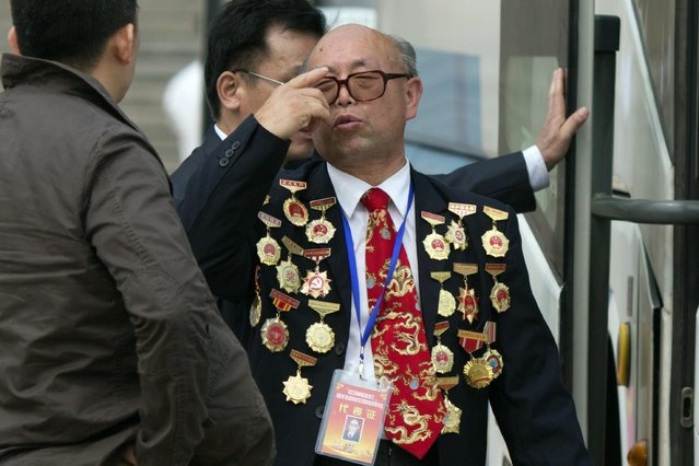 A man covered in medals leave a May Day event to celebrate China's model workers outside the Great Hall of the People in Beijing, Friday, May 1, 2015. Millions of Chinese are taking advantage of the May Day holidays to visit popular tourist sites. (Photo by Ng Han Guan/AP Photo)