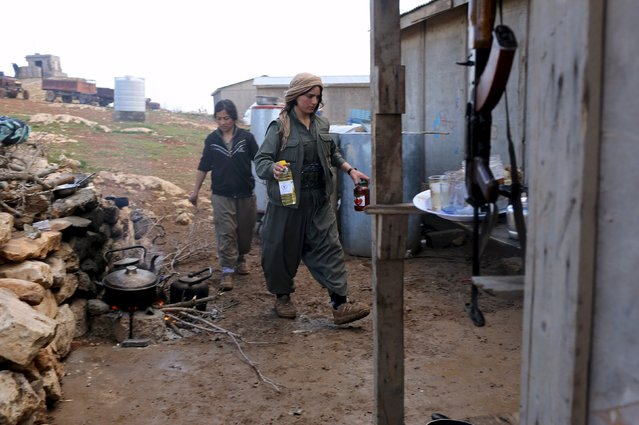 Female Kurdistan Workers Party (PKK) fighters help in an area they use for cooking at a base in Sinjar, March 13, 2015. (Photo by Asmaa Waguih/Reuters)