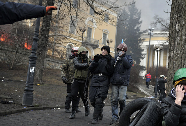 """Protesters escort a """"detained"""" policeman near Independence square in Kiev, on February 20, 2014. (Photo by Louisa Gouliamaki/AFP Photo)"""