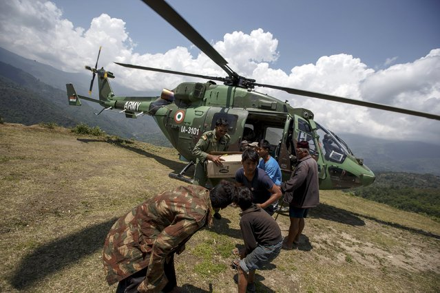 An indian military personnel and earthquake survivors unload relief supplies from an Indian Army helicopter near Sirdibas, Nepal May 2, 2015. (Photo by Athit Perawongmetha/Reuters)