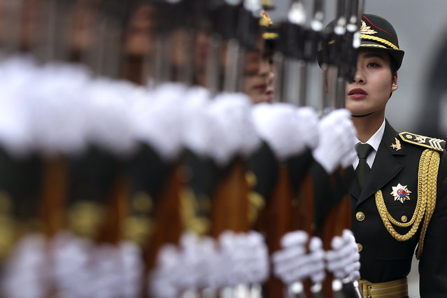 A female Chinese People's Liberation Army soldier looks at members of an honor guard preparing for a welcome ceremony for visiting German President Joachim Gauck, outside the Great Hall of the People in Beijing, Monday, March 21, 2016. (Photo by Andy Wong/AP Photo)
