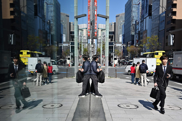 """A businessman (R) runs down the pavement in Tokyo's Ginza district on April 3, 2019. For the Emperor's abdication on April 30, Japanese workers will enjoy an unprecedented 10-day holiday as a rash of special days off combine with the traditional """"Golden Week"""" in May. But not everyone is popping the champagne corks in famously workaholic Japan. (Photo by Charly Triballeau/AFP Photo)"""