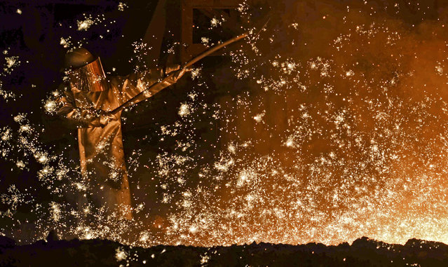A steel-worker is pictured at a furnace at the plant of German steel company Salzgitter AG in Salzgitter, Lower Saxony on March 17, 2015. (Photo by Fabian Bimmer/Reuters)