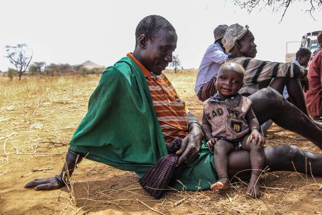 A young dad in Napak district looks after his boy at a community meeting, where people from the village get together and talk about the lack of harvests and water, Karamoja, Uganda, February, 2017. (Photo by Sumy Sadurni/Barcroft Images)