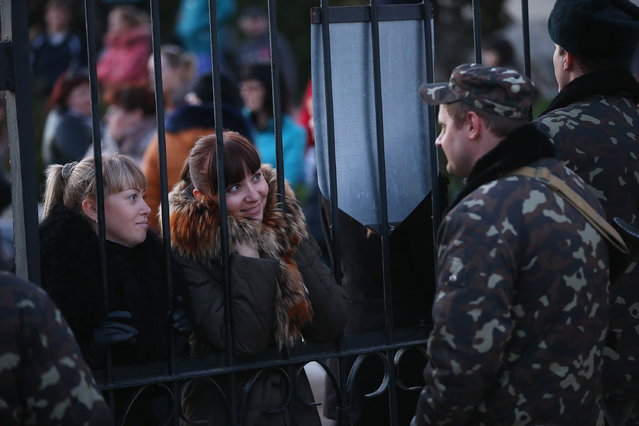 Ukrainian soldiers at the Belbek military base talk friends and family members through the gates of the base entrance on March 3, 2014 in Lubimovka, Ukraine. (Photo by Sean Gallup/Getty Images)