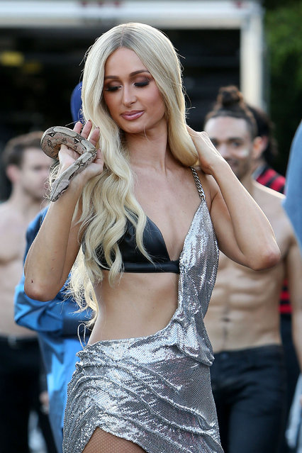 Paris Hilton holds a snake as she's spotted on a shoot in Los Angeles, California on May 3, 2019. Animal lover Paris was seen smiling as she took the snake off the handler and held it around her neck. She seemed delighted to get acquainted with the reptile as she posed up a storm. Dressed in a silver chainlink dress with a cutaway revealing her bra and plenty of flesh she accessorized with high stilettos with a diamant skull detail. (Photo by Splash News and Pictures)