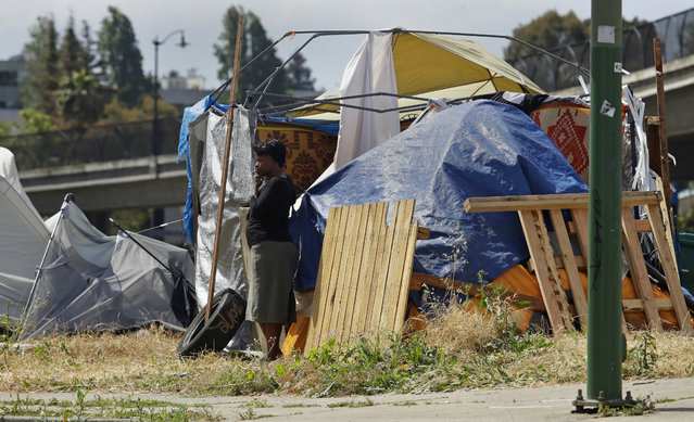 In this photo taken on Friday, May 17, 2019, a woman smokes a cigarette outside a homeless encampment in Oakland, Calif. California Gov. Gavin Newsom is creating a task force on homelessness as the state grapples with a housing crisis. Speaking Tuesday, May 21,  in Oakland, Newsom described homelessness as an epidemic of statewide concern but says it will be best addressed at the local level. (Photo by Ben Margot/AP Photo/File)