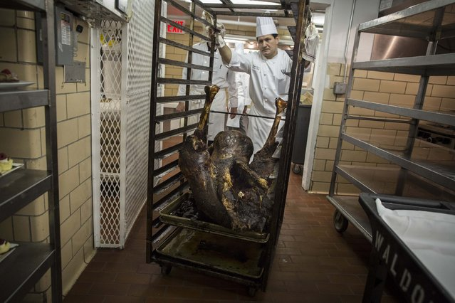 A chef with a tray of roasted ostrich walks through the kitchen before the 110th Explorers Club Annual Dinner at the Waldorf Astoria in New York March 15, 2014. (Photo by Andrew Kelly/Reuters)