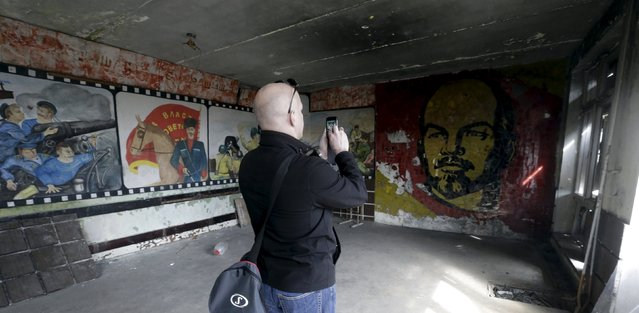 A man takes a picture inside Soviet propaganda room in the ghost town of a former Soviet military radar station near Skrunda, Latvia, April 9, 2016. (Photo by Ints Kalnins/Reuters)