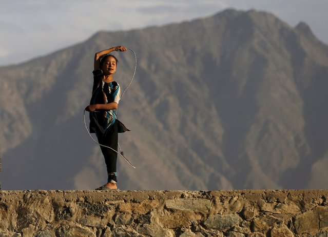 An Afghan girl plays with a rope on a hilltop in Kabul, Afghanistan May 18, 2015. (Photo by Mohammad Ismail/Reuters)