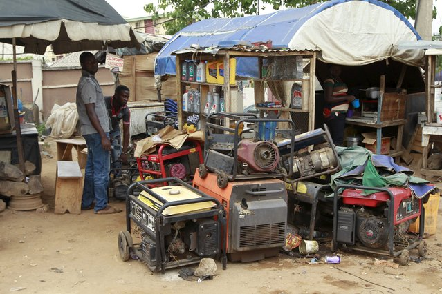 A man is seen working on power generators at the Area 10 shopping centre in Abuja, Nigeria May 25, 2015. (Photo by Afolabi Sotunde/Reuters)
