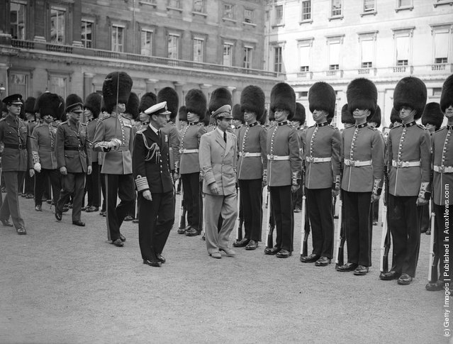 1948:  The Shah of Persia, accompanied by King George VI, inspecting the guard of honour of the 2nd Battalion Coldstream Guards at Buckingham Palace