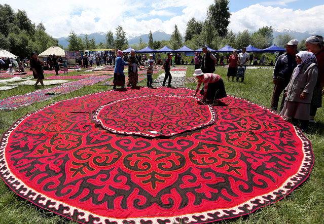People lay out carpets as they attend the 5th International Festival of Kyrgyz National Applied Arts in the village of At-Bashi, Naryn province, 400 km from Bishkek, Kyrgyzstan, 28 June 2015. Craftsmen from all over Kyrgyzstan took part in the festival which received support from the German Federal Enterprise for International Cooperation. (Photo by Igor Kovalenko/EPA)