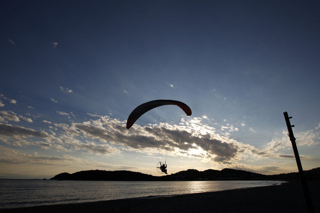 A paraglider flies over the beach of Anavyssos near Athens on Saturday, April 12, 2014. In a statement Friday, finance ministers and central bankers from the Group of 20 wealthy and developing nations state they believe an ambitious goal to boost global growth by $2 trillion in the next five years is within reach. (Photo by Kostas Tsironis/AP Photo)