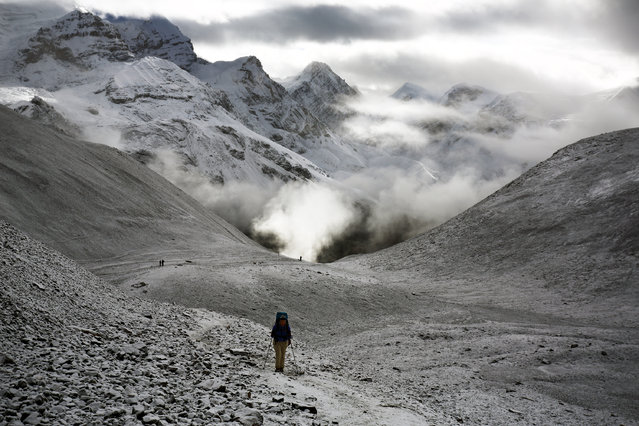 """""""Up High in the Himalayas"""". A woman makes her way up toward Thorong La Pass. At 17,769 feet, Thorong La Pass is the highest point along the Annapurna Circuit in Nepal. This is a full color image. Photo location: Thorong La Pass, Nepal. (Photo and caption by Ed Graham/National Geographic Photo Contest)"""