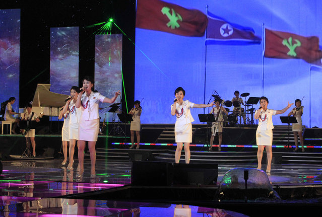 In this Friday, March 28, 2014 photo, singers of the Moranbong Band perform on their stage in Pyongyang, North Korea. Step aside, Sea of Blood Opera. North Korean leader Kim Jong Un's favorite guitar-slinging, miniskirt-sporting girl group, the Moranbong Band, is back. And these ladies know how to shimmy. (Photo by Jon Chol Jin/AP Photo)