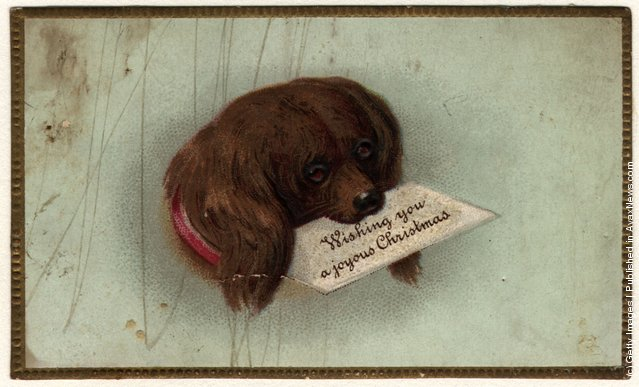 1860: A Victorian  Christmas card showing a dog carrying Christmas greetings in his mouth