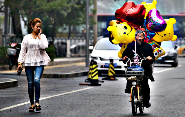 A balloon-seller cycles along a street during wet weather in Beijing on June 7, 2013. (Photo by Ed Jones/AFP Photo)