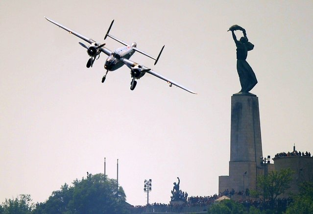 "A pilot in US B-25 Mitchell bomber from1945 flies beside the ""Freedom"" statue at the Gellert Hill on May 1, 2014 during a Red Bull flying and car show around the Danube River of Budapest downtown. (Photo by Attila Kisbenedek/AFP Photo)"