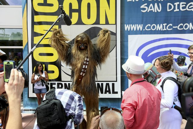 A man dressed as Chewbacca from Star Wars poses with fans outside of the 2015 Comic-Con International in San Diego, California, July 9, 2015. (Photo by Sandy Huffaker/Reuters)