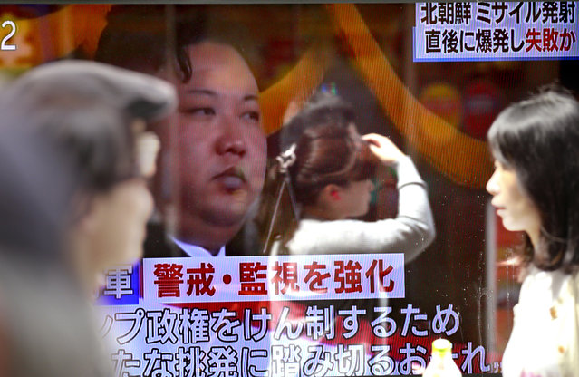 """People walk past a TV news showing an image of North Korean leader Kim Jong Un while reporting North Korea's rocket launch, in Tokyo, Sunday, April 16, 2017. A North Korean missile exploded during launch Sunday from the country's east coast, U.S. and South Korean officials said, a high-profile failure that comes as a powerful U.S. aircraft carrier approaches the Korean Peninsula in a show of force. The letters on the top read """"North Korea's missile might have exploded and failed soon after launch"""". (Photo by Shizuo Kambayashi/AP Photo)"""