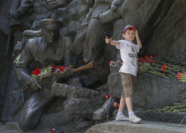 A little boy plays on a bronze monument of the open-air memorial museum for WW II in downtown Kiev, Ukraine, 09 May 2014. People of former USSR countries celebrate the 69th anniversary of the victory over Nazi Germany in World War II. (Photo by Sergey Dolzhenko/EPA)
