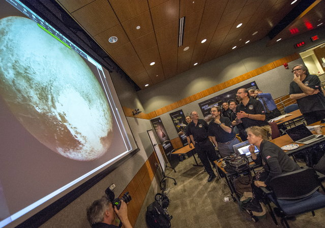 Members of the New Horizons science team react to seeing the spacecraft's last and sharpest image of Pluto before closest approach later in the day at the Johns Hopkins University Applied Physics Laboratory (APL) in Laurel, Maryland July 14, 2015. (Photo by Bill Ingalls/Reuters/NASA)