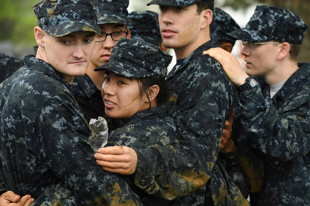 United States Naval Academy plebe, Catalina Rico, left center, huddles with others to keep warm during Sea Trials at the United States Naval Academy on Tuesday May 17, 2016 in Annapolis, MD. (Photo by Matt McClain/The Washington Post)