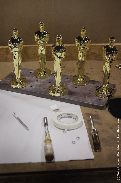 Oscar statuettes sit on a work bench prior to being assembled at R.S. Owens & Company