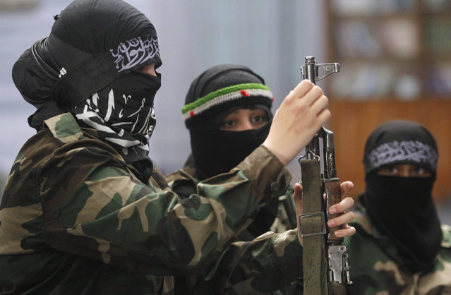 A female member of the Ahbab Al-Mustafa Battalion holds a rifle during military training in a mosque in the Seif El Dawla neighbourhood in Aleppo June 24, 2013. (Photo by Muzaffar Salman/Reuters)
