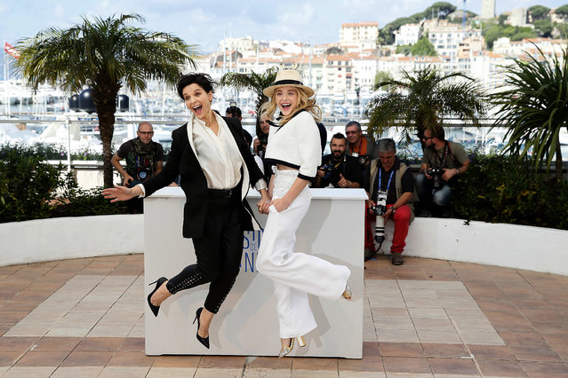 Actress Juliette Binoche, left, and actress Chloe Grace Moretz jump for photographers during a photo call for Sils Maria at the 67th international film festival, Cannes, southern France, Friday, May 23, 2014. (Photo by Alastair Grant/AP Photo)