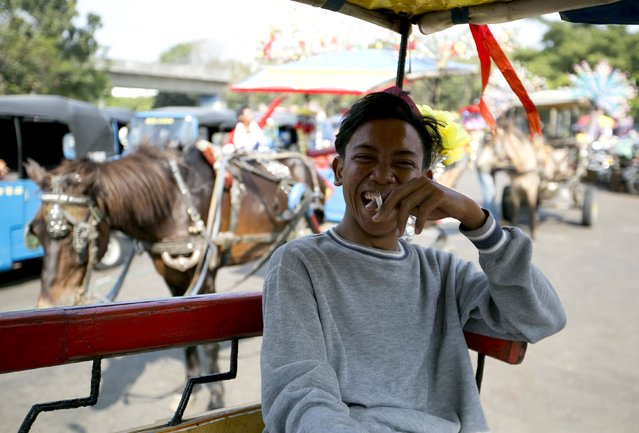 A horse and buggy driver smokes while waiting for customers near Monas, the national monument, in Jakarta, Indonesia, July 21, 2015. Indonesians are smoking less than before, and that poses a dilemma for a government that faces a budget shortfall as well as rising unemployment and counts on tobacco taxes for about 10 percent of state revenue. (Photo by Darren Whiteside/Reuters)